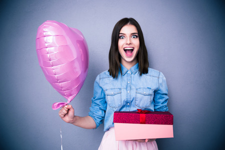 holding the head: Amazed woman holding balloon and gift box over gray background. Looking at camera.