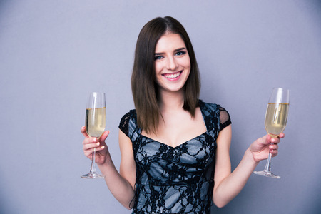Smiling woman holding two glass of champagne over gray background. Looking at camera. Wearing in dress photo