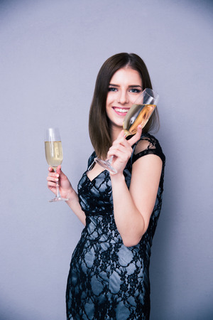 Happy woman holding two glass of champagne and looking at camera over gray background. Wearing in dress photo