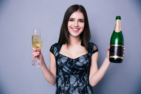Smiling woman holding two glass and bottle of champagne over gray background. Looking at camera. Wearing in dress photo