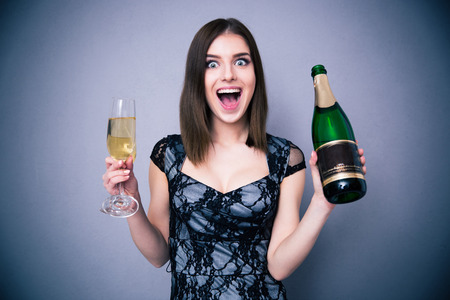 celebrating: Happiness woman holding two glass and bottle of champagne over gray background. Wearing in dress. Looking at camera Stock Photo