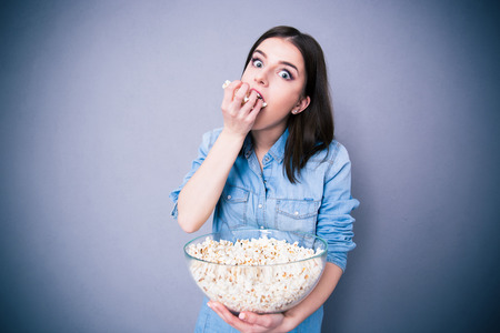 eating: Young cute woman eating popcorn over gray background. Looking at camera