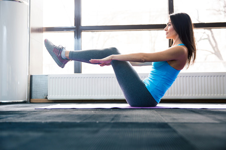 lying on stomach: Happy young woman doing exercise on yoga mat at gym Stock Photo