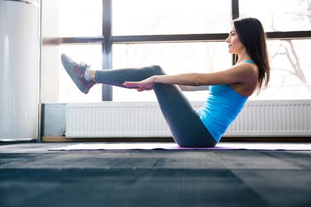 haciendo ejercicio: Mujer joven feliz haciendo ejercicio en estera de yoga en el gimnasio