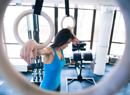 relaxed woman: Tired woman working out on gimnastick rings at gym