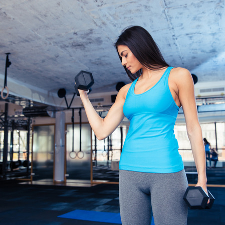 concetrated: Cute woman working out with dumbbells at gym