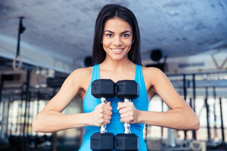 Happy fit woman holding dumbbells at gym 版權商用圖片 - 38584068