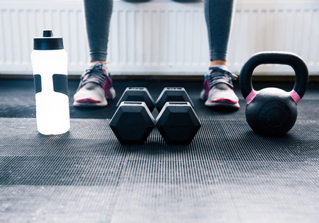 Closeup image of a woman sitting at gym with dumbbells, shaker and weight Foto de archivo