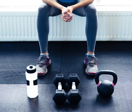 gym floor: Closeup image of a woman sitting at gym with dumbbells, shaker and weight Stock Photo
