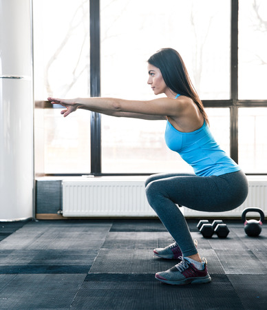 Side view portrait of a young woman doing squats at fitness gym