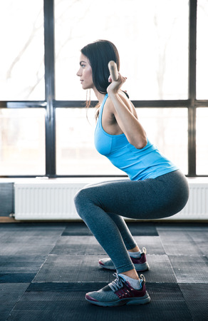 knee bend: Side view portrait of a young woman doing squats with barbell at fitness gym Stock Photo