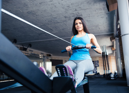 concetrated: Happy charming woman working out on training simulator in fitness gym