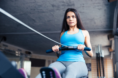 Attractive young woman working out on training simulator at fitness gym Stock Photo