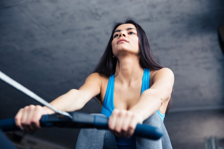 concetrated: Beautiful woman working out on training simulator in fitness gym