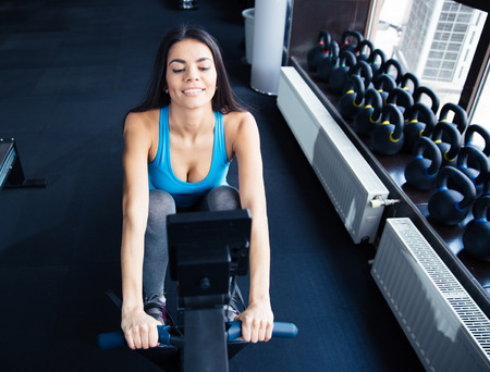 Happy young cute woman working out on a simulator at gym Stock Photo