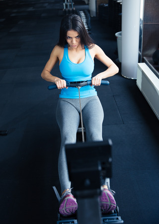 simulator: Young woman doing exercise on a simulator at gym