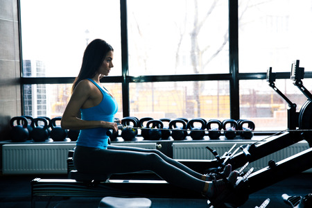 concetrated: Side view portrait of a beautiful woman working out on simulator at gym Stock Photo
