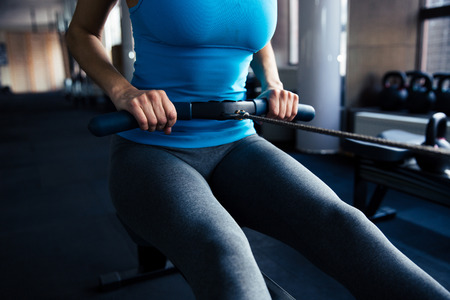 simulator: Closeup image of a woman working out on simulator at gym