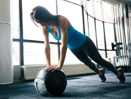fit ball: Cute attractive young woman working out with fit ball at gym Stock Photo