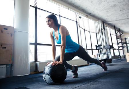 haciendo ejercicio: Mujer joven que hace ejercicio con la pelota en forma en el gimnasio