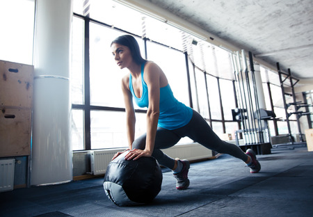 fit ball: Young woman doing exercise with fit ball at gym