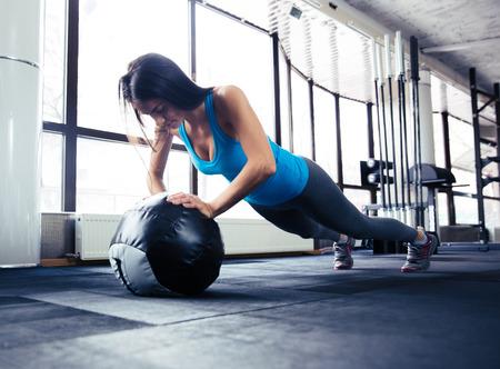 Jonge vrouw doet push up op fit bal op sportschool