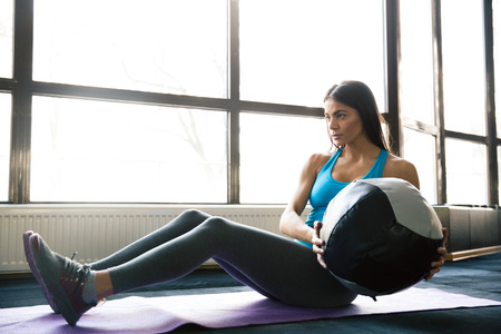fit ball: Young sports woman working out with fit ball on yoga mat at gym Stock Photo