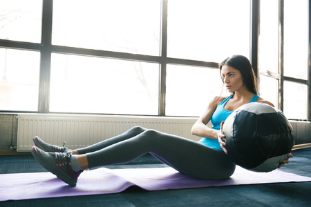 fit ball: Young beautiful woman working out with fit ball on yoga mat at gym Stock Photo