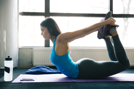 yoga class: Young fit woman stretching on yoga mat at gym
