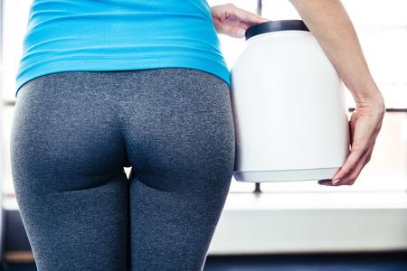 Terug portret van vrouwelijk lichaam met sportvoeding op sportschool