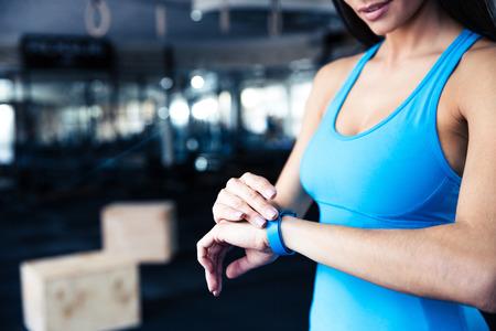 Vrouw met behulp van activiteit tracker op sportschool Stockfoto