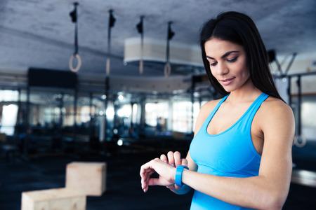 deporte: Mujer joven feliz que usa la actividad de seguimiento en el gimnasio de fitness