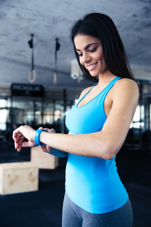 sports activities: Smiling young woman using activity tracker at gym