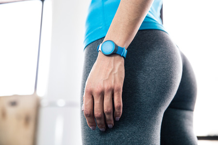 Side view portrait of female body with fitness tracker