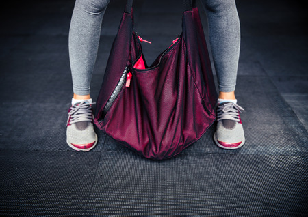 Closeup image of a female legs and sports bag