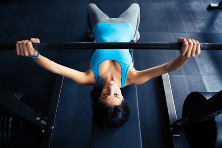 human chest: Young fit woman working out with barbell on bench in the gym. Bar Bench Pres Stock Photo