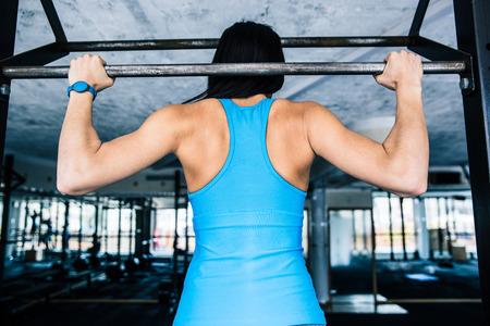 haciendo ejercicio: Vista trasera retrato de una mujer en forma de trabajo en el gimnasio