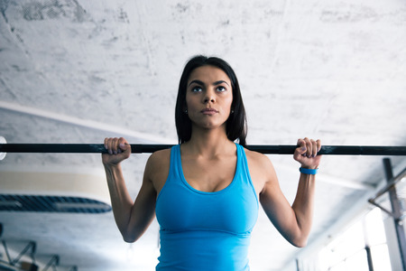 Beautiful fit woman working out with barbell at gym Stock Photo