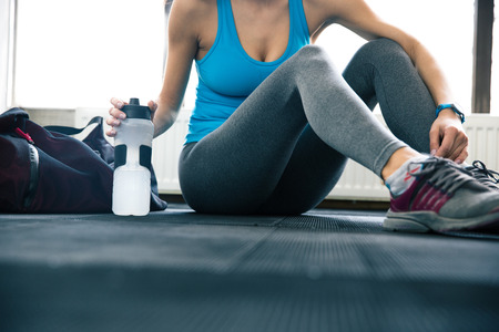 body bag: Fit woman sitting on the floor at gym