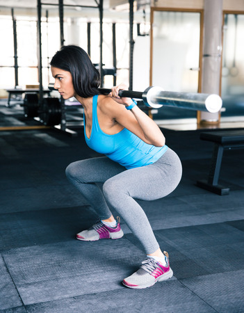 concetrated: Young fit woman working out with barbell at gym