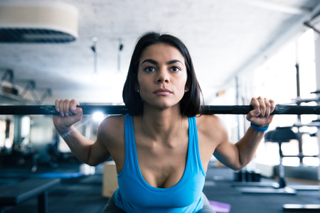 concetrated: Attractive young woman working out with barbell at gym Stock Photo