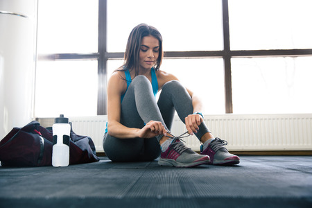 Beautiful woman tying shoelaces at gym