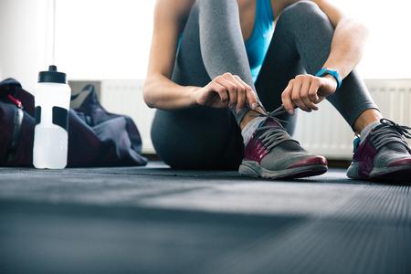 deporte: Mujer que ata los cordones en el gimnasio