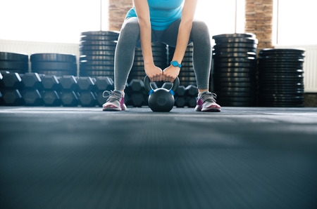 lift hands: Woman working out with kettle ball at gym