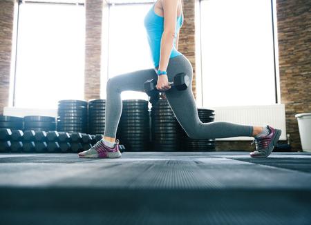 levantando pesas: Imagen del primer de una mujer que trabaja con pesas en el gimnasio