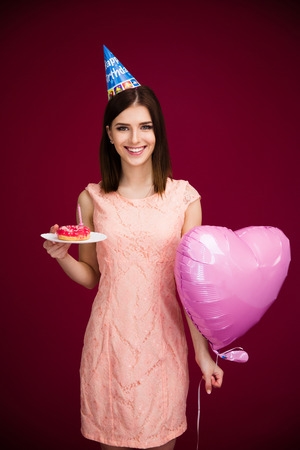 birthday adult: Woman holding heart shaped balloon and donut with candle over pink background. Looking at camera. Wearing in dress. Celebrating birthday