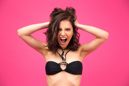Angry woman in bikini shouting  over pink background. Looking at camera Stock Photo