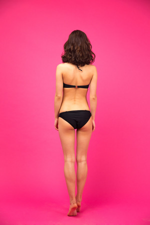 pink bikini: Back view portrait of a woman in bikini posing over gray background