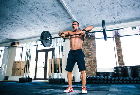 concetrated: Full length portrait of a muscular man lifting barbell at gym