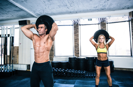 human muscle: Muscular man and fit woman workout at crossfit gym Stock Photo